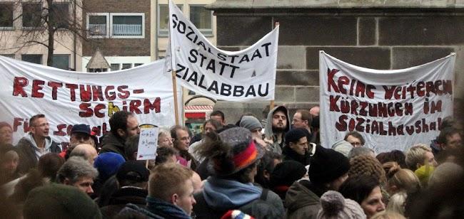 Protestdemo gegen Kürzungen. Transparente, zum Beispiel: »Keine weiteren Kürzungen im Sozialhaushalt!«, »Sozialstaat statt Sozialabbau«.
