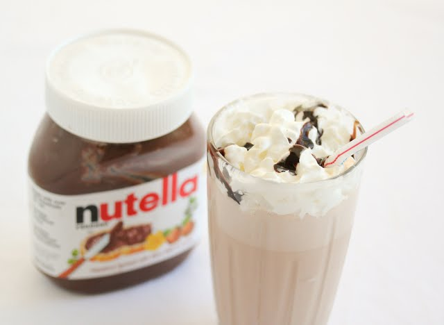 photo of a nutella milkshake with a jar of nutella behind it
