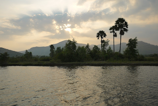 mountains, tropical trees, and a river with a setting sun