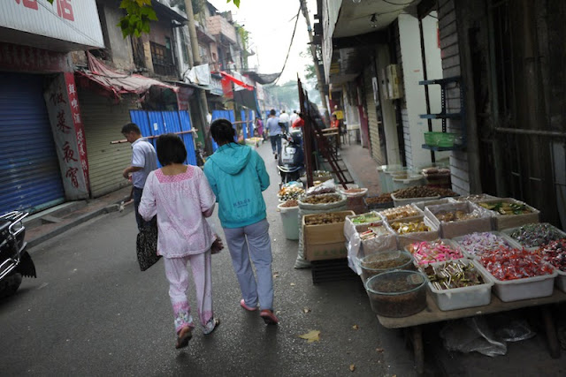 two young women walking by food items for sale at Beizheng Street in Changhsa