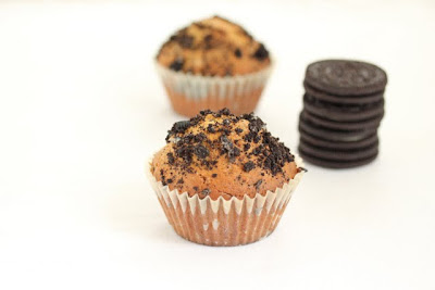 photo of two oreo muffins with a stack of oreos