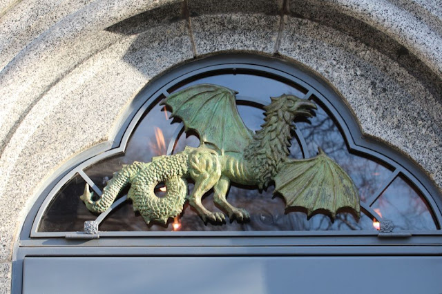 a gryphon in sculpture framed in a stone archway