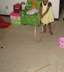 Hoop rolling with hula hoop and stick