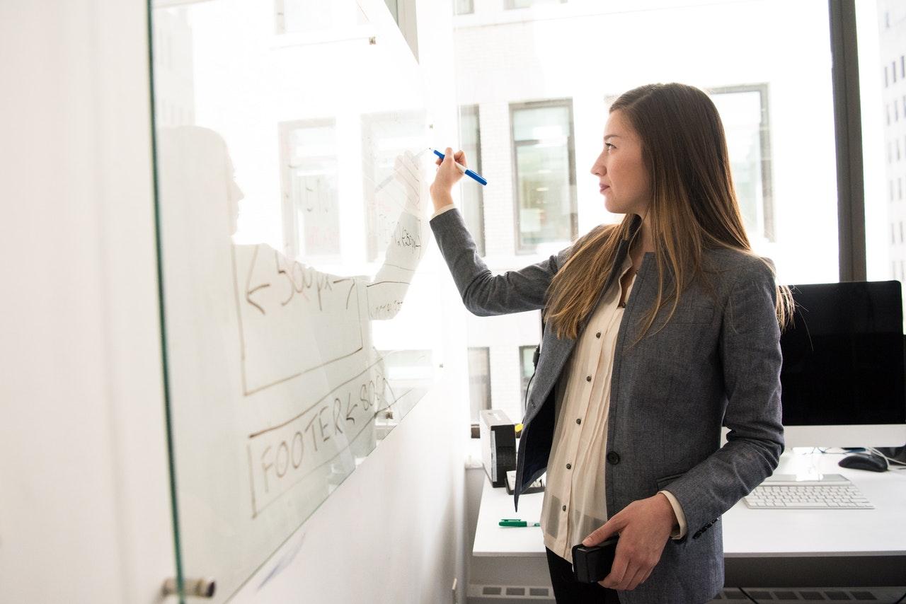 Woman wearing gray blazer writing on dry erase board.