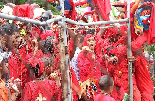 Diablos de Yare apiñados contra una cerca en el día de Corpus Christi en San Francisco de Yare, Municipio Bolivar, Miranda Venezuela