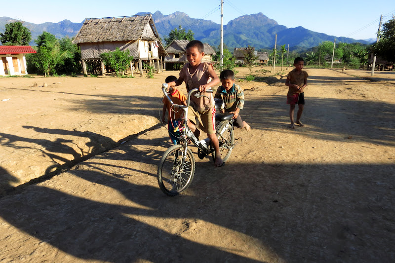 Village kids playing on a bike