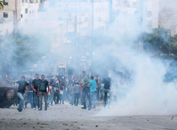 Palestinian police fire tear gas on demonstrators protesting against increased prices (photo: Reuters)