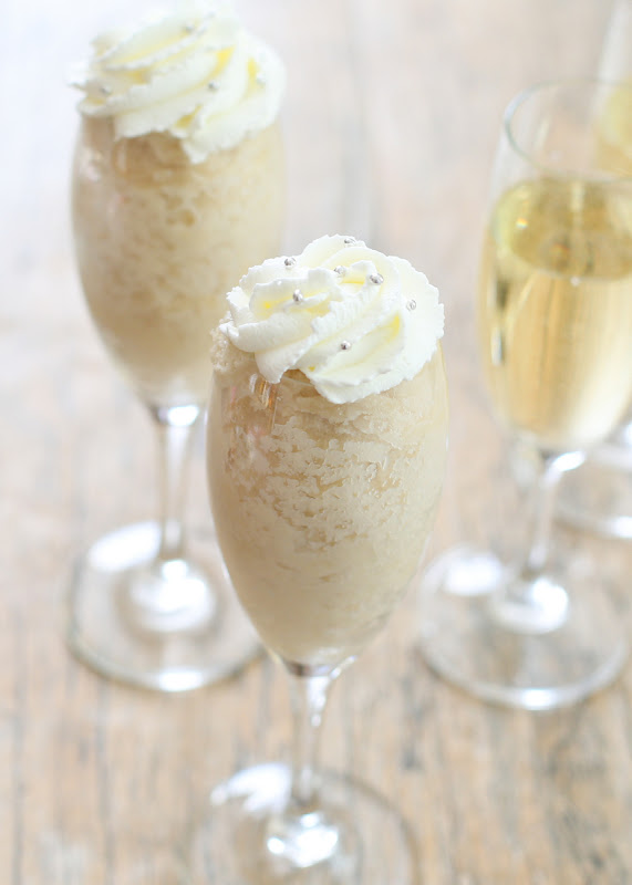 photo of two champagne mug cakes in champagne glasses topped with whipped cream and silver sprinkles