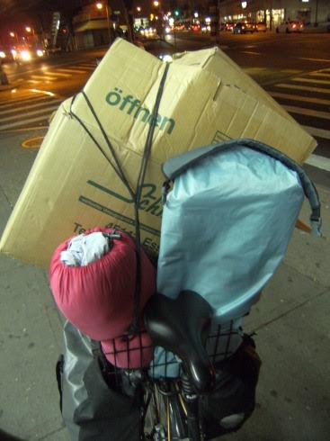 Umzugskartons von Walter Schmitz Möbeltransporte und Umzüge aus Essen, Zelt und Schlafsack im Basil-Korb auf Panther Dominance Trekking bei der Nachtfahrt durch Queens, New York City