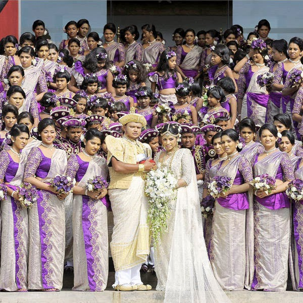 Sri Lankan wedding couple Nisansala (R) and Nalin (L) pose for photographers alongside their bridesmaids during their Guinness World Record-breaking wedding in Negombo, some 30kms north of Colombo, on November 8, 2013. The Sri Lankan couple created a new record with 126 bridesmaids in their wedding group.