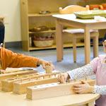 Preschool children at Irvine Montessori school working together with cylinder blocks.