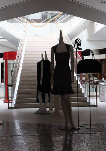 mannequins with pointy necks and no heads, back-lit by a Y-shaped white staircase