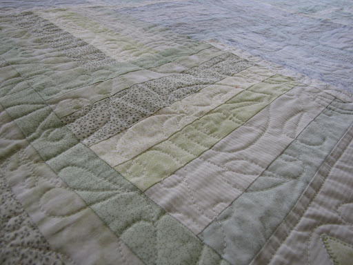 Machine-quilted leaves pick up the border motif within the quilt.