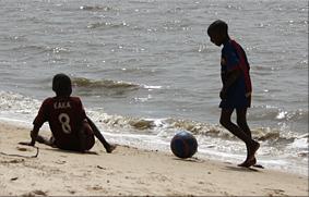 Niños jugando al futbol en la playa