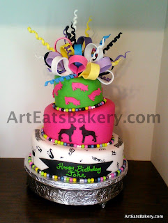 Pink, white, black, green and yellow mad hatter topsy turvery birthday cake. It is decorated with Great Dane dogs, music notes, instruments, pigs and fondant pearls with bow and curls topper