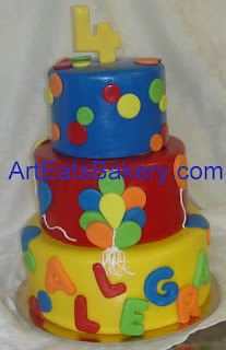 Three tier fondant custom kids birthday cake with polka dots, balloons, the birthday girls name and a 4 topper