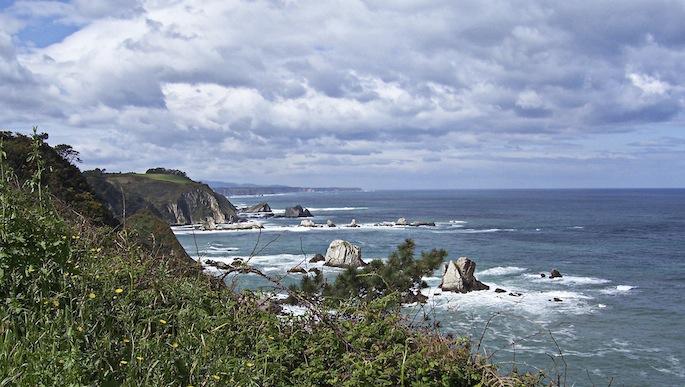 Paisaje de un acantilado marino con vegetación y nubes