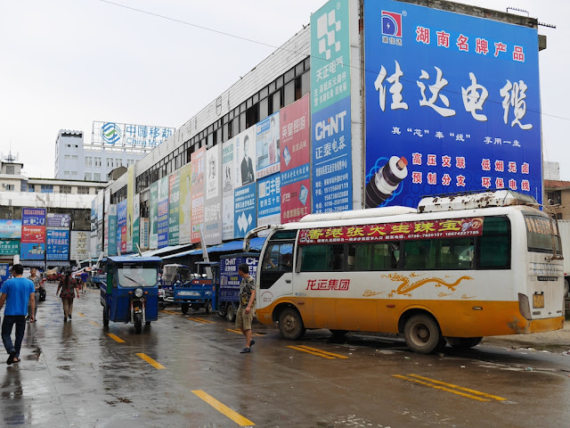 bus parked on the side of a road next to a shopping center in Changde
