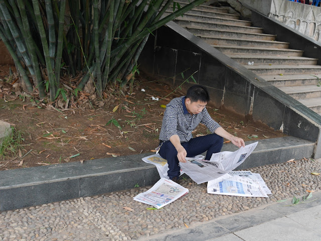 man reading a newspaper in Hengyang, Hunan, China
