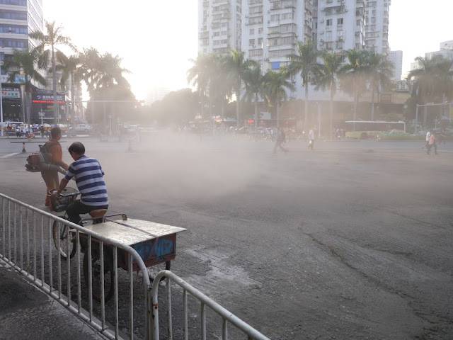 man riding a tricycle cart through a dust cloud created by a gravelblower