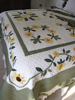 A second, appliqued quilt in the same colors drapes the bottom of the previous