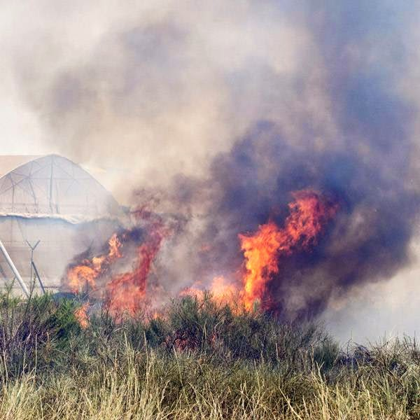 Fire consumes a field close to greenhouses on a farm in the Israeli Mediterranean coastal city of Ashkelon after a rocket fired by Palestinian militants from the Gaza Strip landed there, on July 15, 2014.