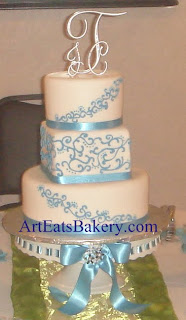 Three tier round and square white fondant wedding cake with blue curlicue scroll design, ribbons and silver monogram
