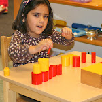 Preschool girl working with Montessori knobless cylinder sensorial material at Huntington Beach private school.