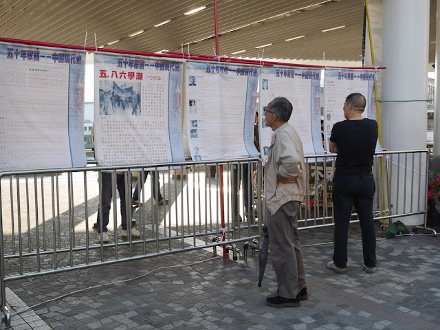 men reading information posted by Hong Kong Alliance in Support of Patriotic Democratic Movements in China
