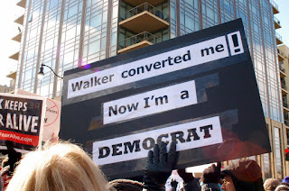 A gloved hand is holding up a black sign with taped-on white pieces of paper with black writing on them: 'Walker converted me! Now I'm a DEMOCRAT'. There is a tall building behind, and a blonde head in the foreground.
