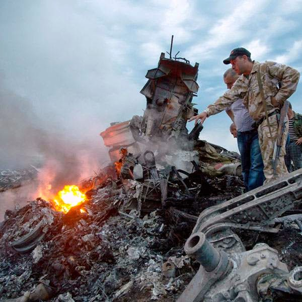 People inspect the crash site of a passenger plane near the village of Grabovo, Ukraine, Thursday, July 17, 2014.