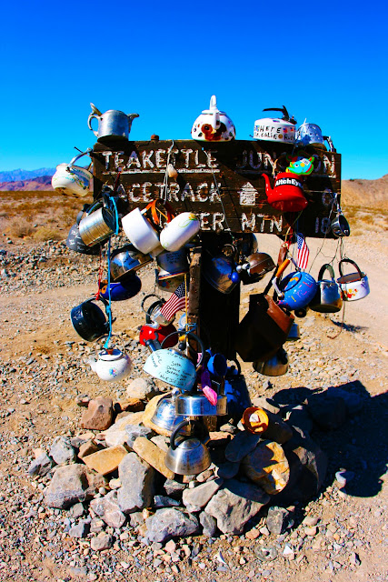 A teakettle covered road sign called Teakettle Junction in Death Valley National Park.