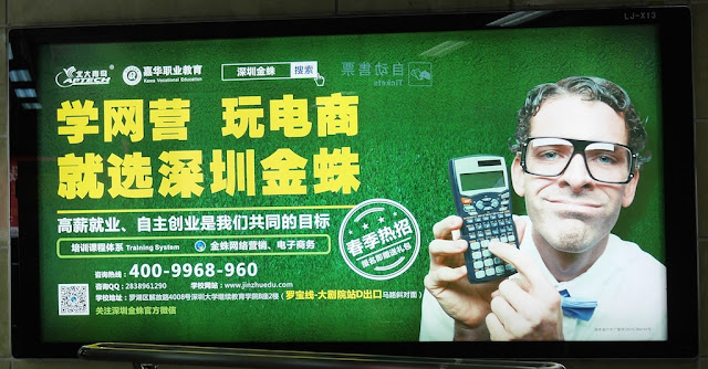 sign with a Caucasian man wearing glasses and holding a scientific calculator