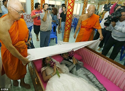 PHOTOS: weird Buddhist religion where couples get married in coffins for goodluck.