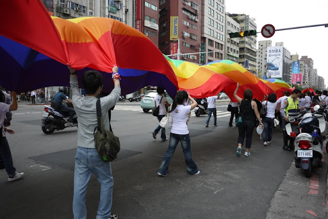 people holding up a large waving rainbow banner