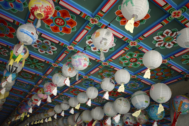 lanterns handing from a colorful ceiling at Bongeunsa Temple in Seoul