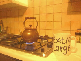 antique small copper kettle on gas cooker next to extra large mug, which it fills comfortably