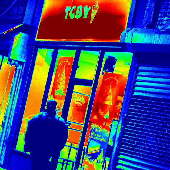 A pedestrian walks by a TCBY frozen yogurt shop at night on the streets of New York City. photo/ps