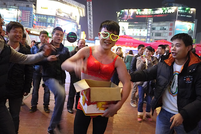 young man wearing red women's underwear and glowing heart glasses in Changsha, China