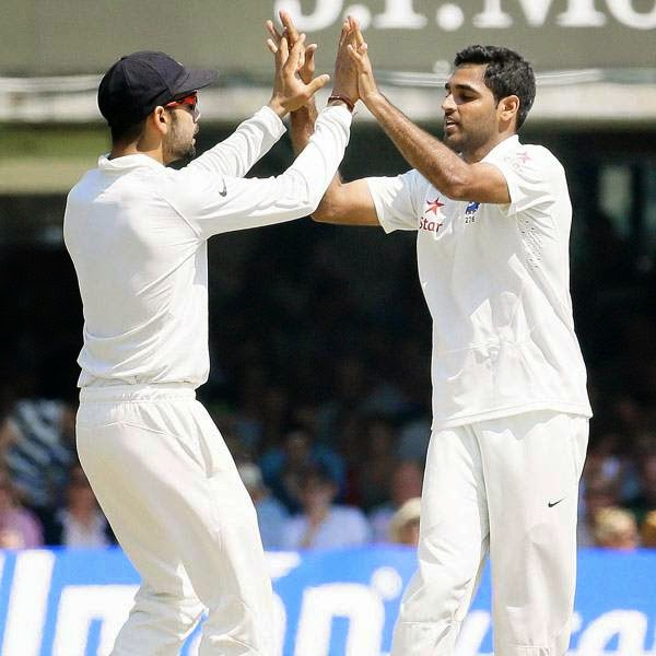 India's Virat Kohli, left, and Bhuvneshwar Kumar celebrate taking the wicket of England's captain Alastair Cook during the second day of the second test match between England and India at Lord's cricket ground in London, Friday, July 18, 2014.