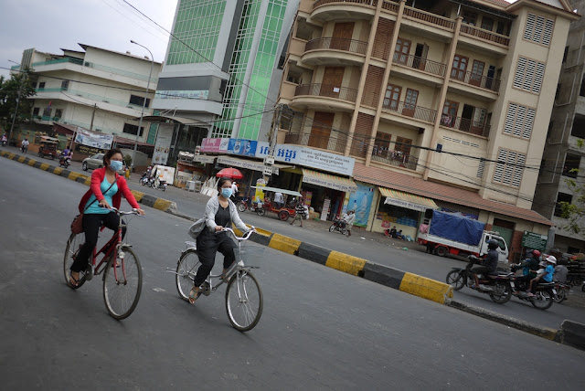 two young women wearing face masks while riding bicycles
