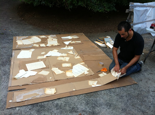 Javier Avila details one cardboard wall of the Voodoo Shanty using pages of old books and sheet music.