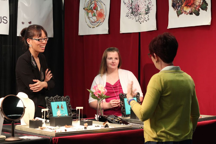 two jewelers talking with another artist