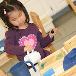 Hands-on materials, often involving many senses, help children acquire advanced scientific vocabulary at an early age, and understand what they learn. This girl is learning about land and waterforms, a peninsula an a chain of lakes, by pouring water around land.