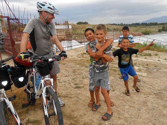 Chris on the Bike mit kirgisischen Jugendlichen auf der Suche nach einem Platz zum Zelten