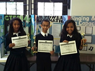 Science Fair 8th Grade Winnders: First Place: Naod Araya (center)  Second Place: Samrawit Areki (left)  Third Place: Shlan Tekeste (right)