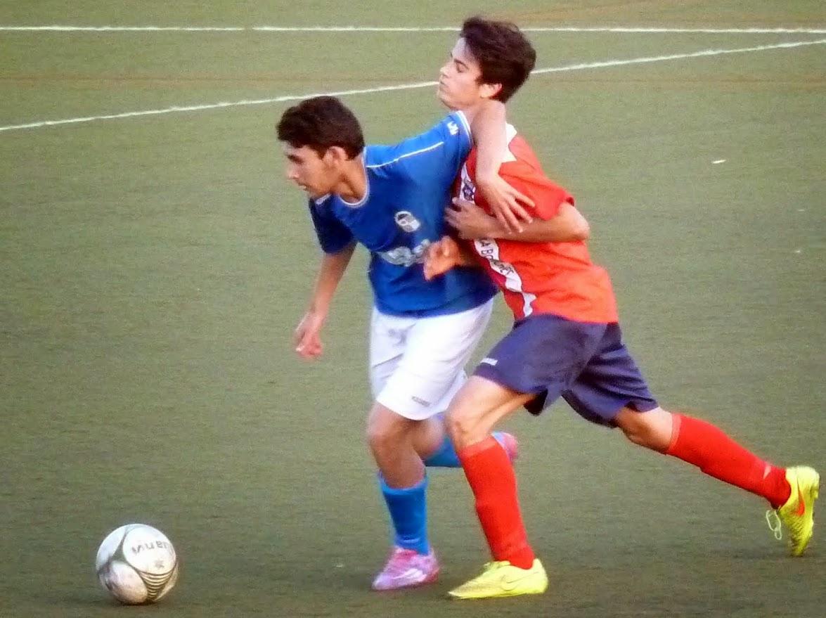 Mario, jugador del Juvenil A en un lance de juego ante un jugador del Fuengirola los Boliches