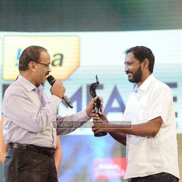 UTV's Dhananjayan present the Best Lyrics award in Tamil to Na Muthukumar for the song 'Aandha Yazhai' from the film 'Thanga Meengal' during the 61st Idea Filmfare Awards South, held at Jawaharlal Nehru Stadium in Chennai, on July 12, 2014.