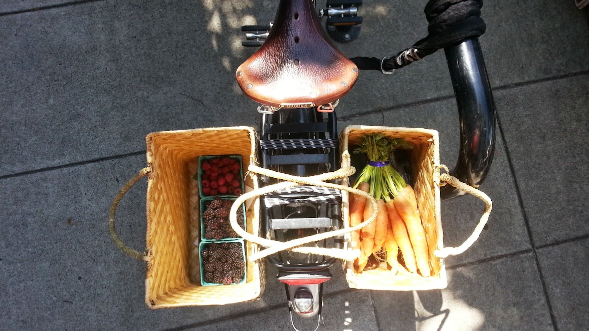 View from above of two baskets of farmers market produce clipped to the rear rack of DarkEm's Dutch bike