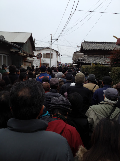 A large crowd walks down the street